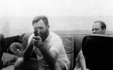 Ernest Hemingway a bord del seu vaixell 'Pilar' apuntant amb una pistola, l'any 1935