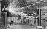Nikola Tesla assegut davant d'una bobina